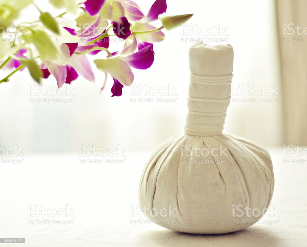 Thai herbal compress ball sitting next to flowers stock photo