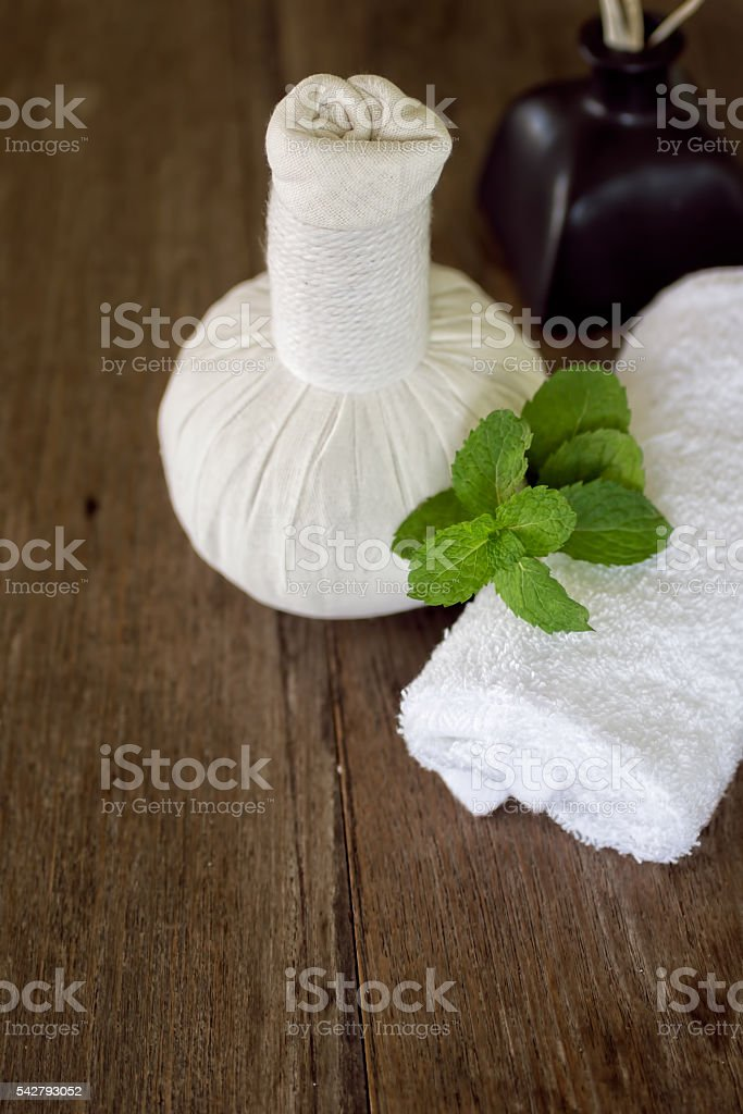 Thai herbal compress, white towel and mint on wooden table stock photo