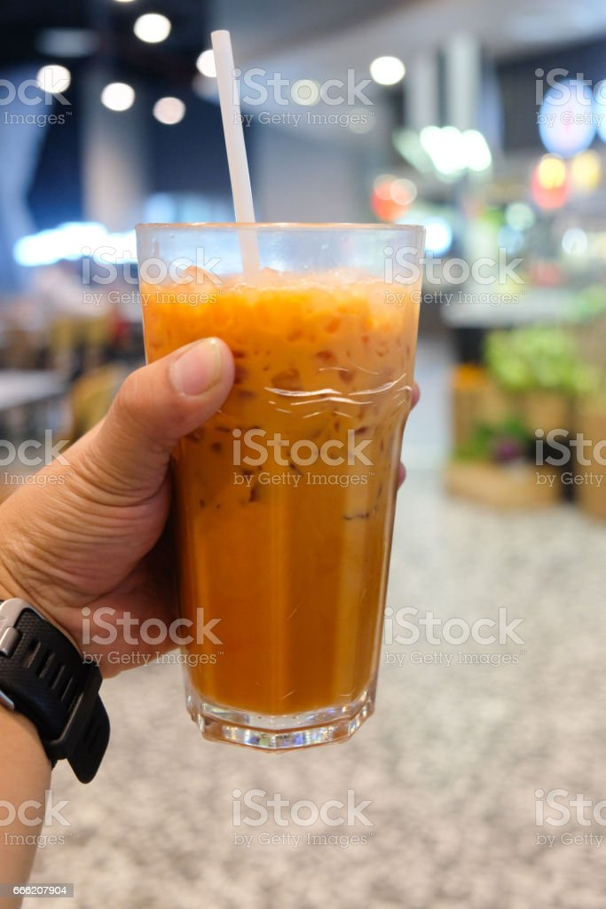 Thai Ice milk tea traditional Thai style in hand stock photo
