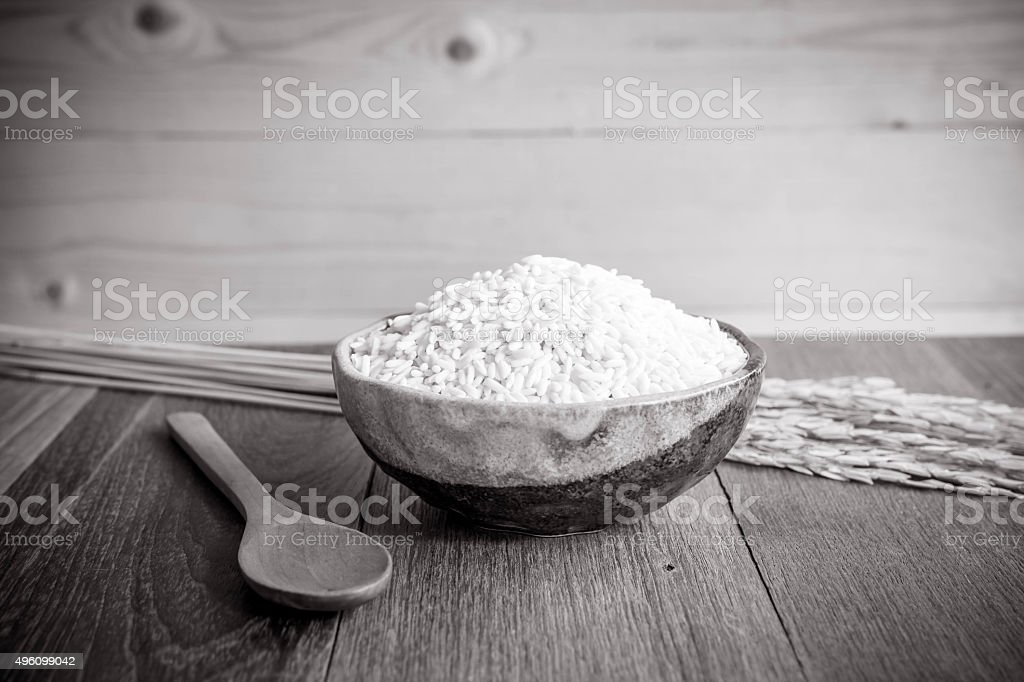 Thai jasmine rice in ceramic cup  and wooden spoon stock photo