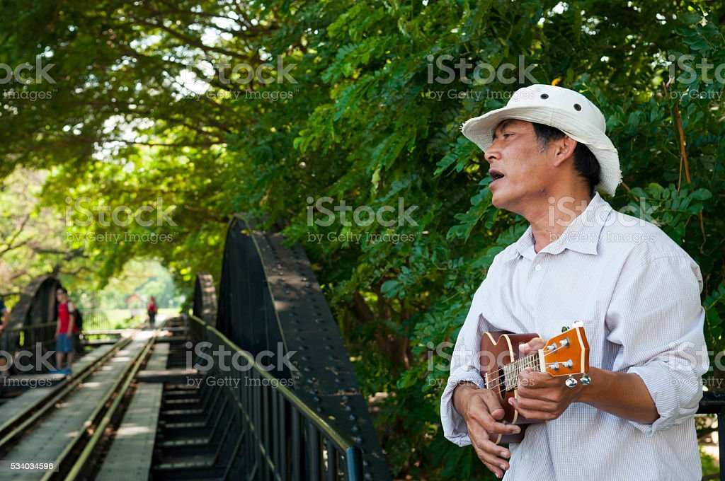 Thai man playing ukulele at Bridge on the River Kwai stock photo