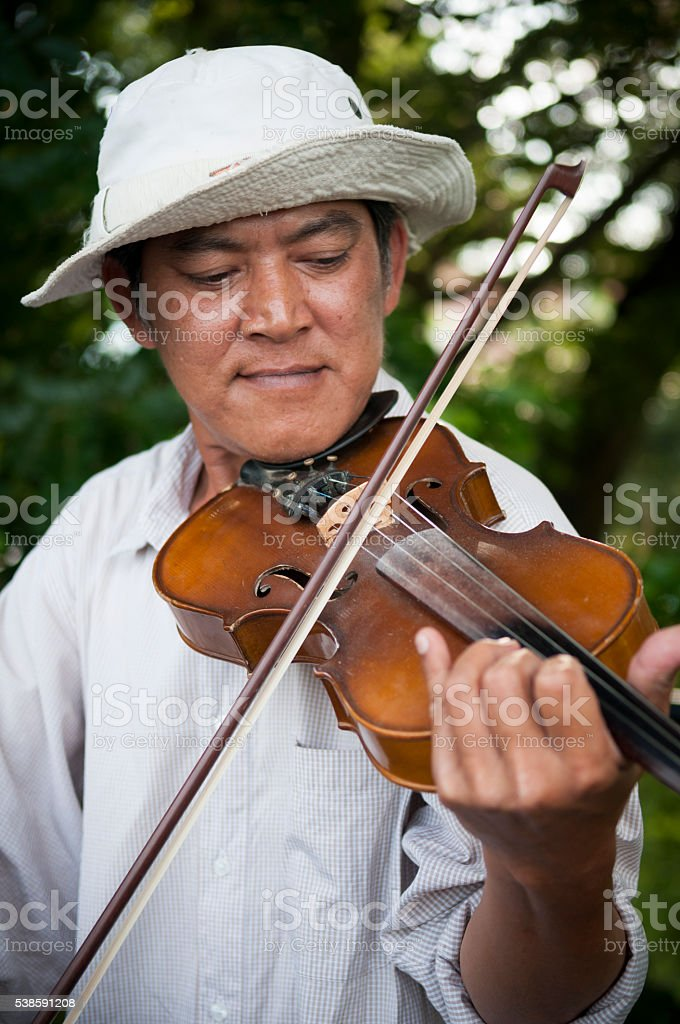 Thai man playing violin on Bridge on the River Kwai stock photo