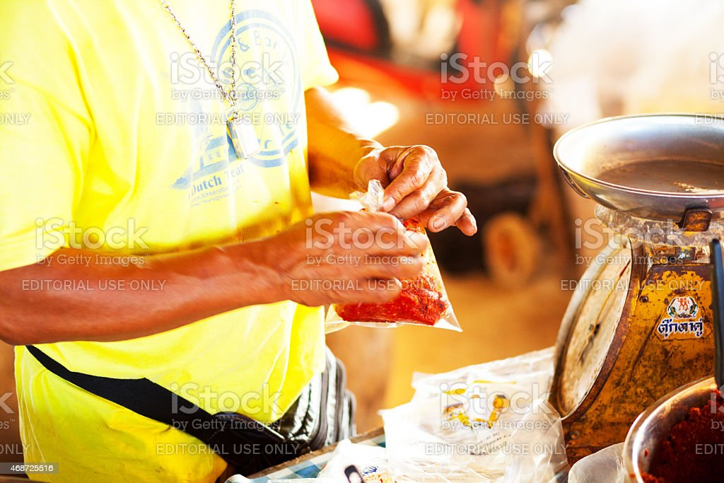 Thai market vendor is packing red chile pastry stock photo
