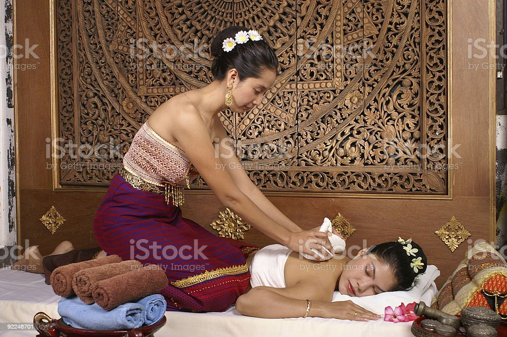 A Thai masseuse giving a massage to a woman stock photo