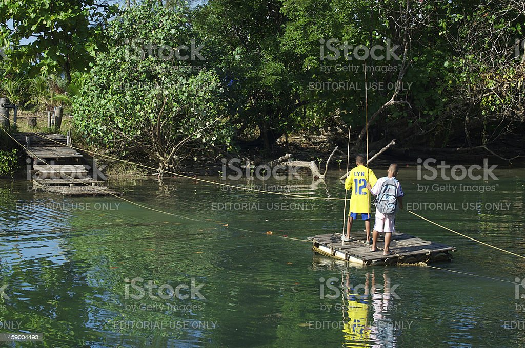 Thai Men Pull Wooden Raft Across Jungle Lagoon Thailand royalty-free stock photo