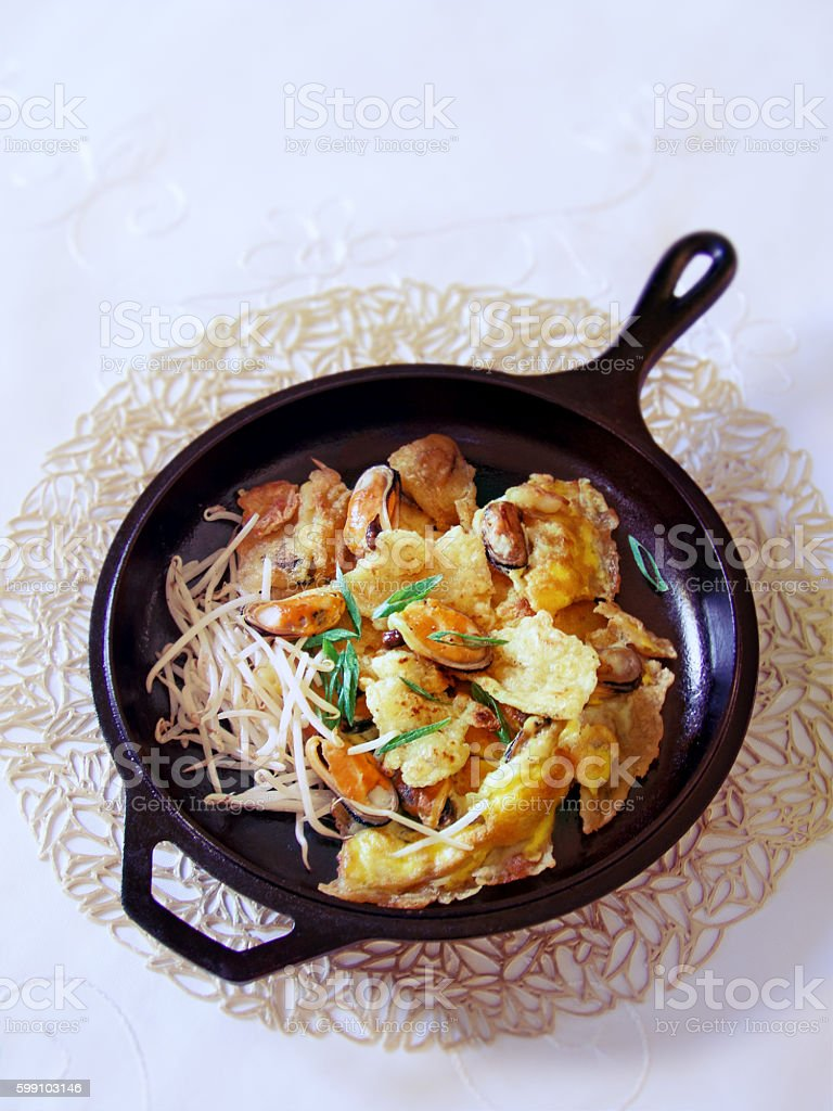 Thai mussel omelette in a cast iron pan vertical stock photo