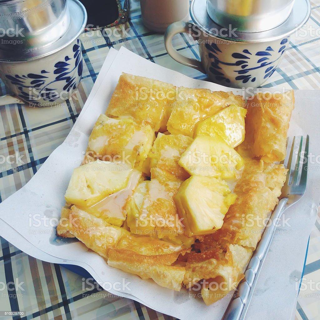 Thai pancake roti with pineapple and condensed milk. stock photo