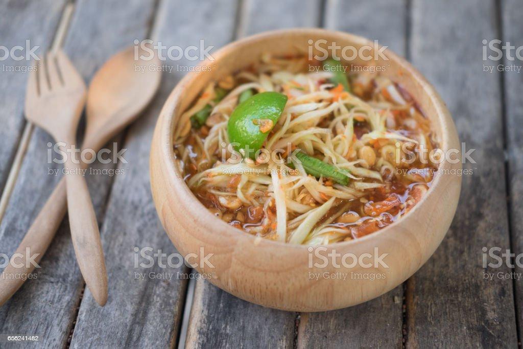Thai Papaya Salad (Som tum Thai) in wood bowl stock photo