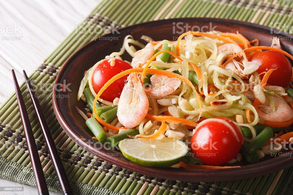 Thai papaya salad with shrimp close-up on a plate. horizontal stock photo