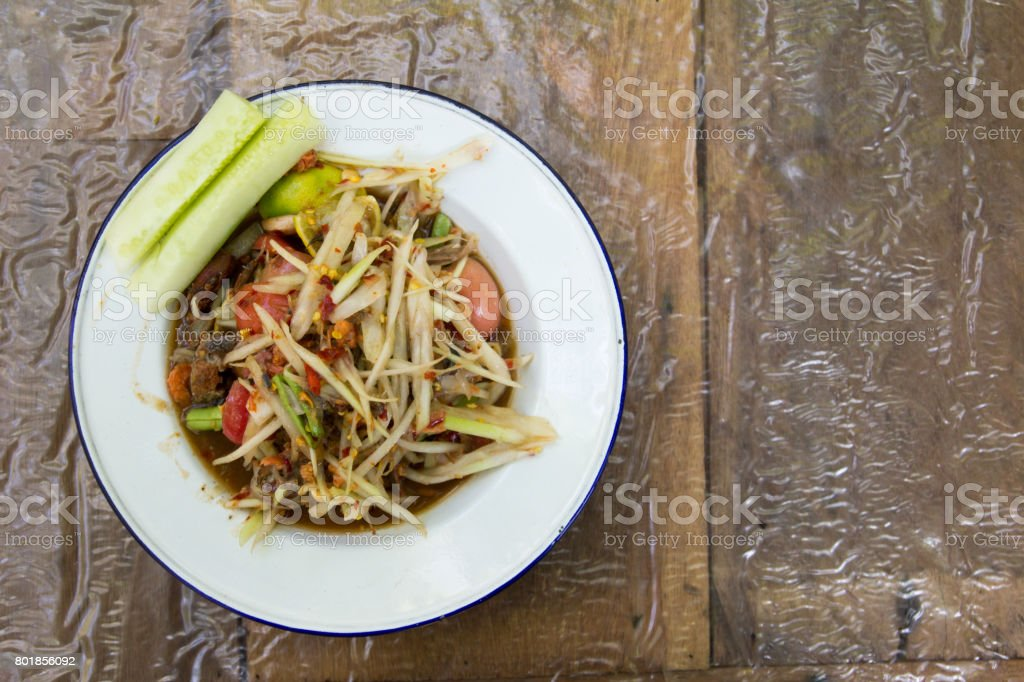 Thai papaya sald (Somtum) on wooden background stock photo