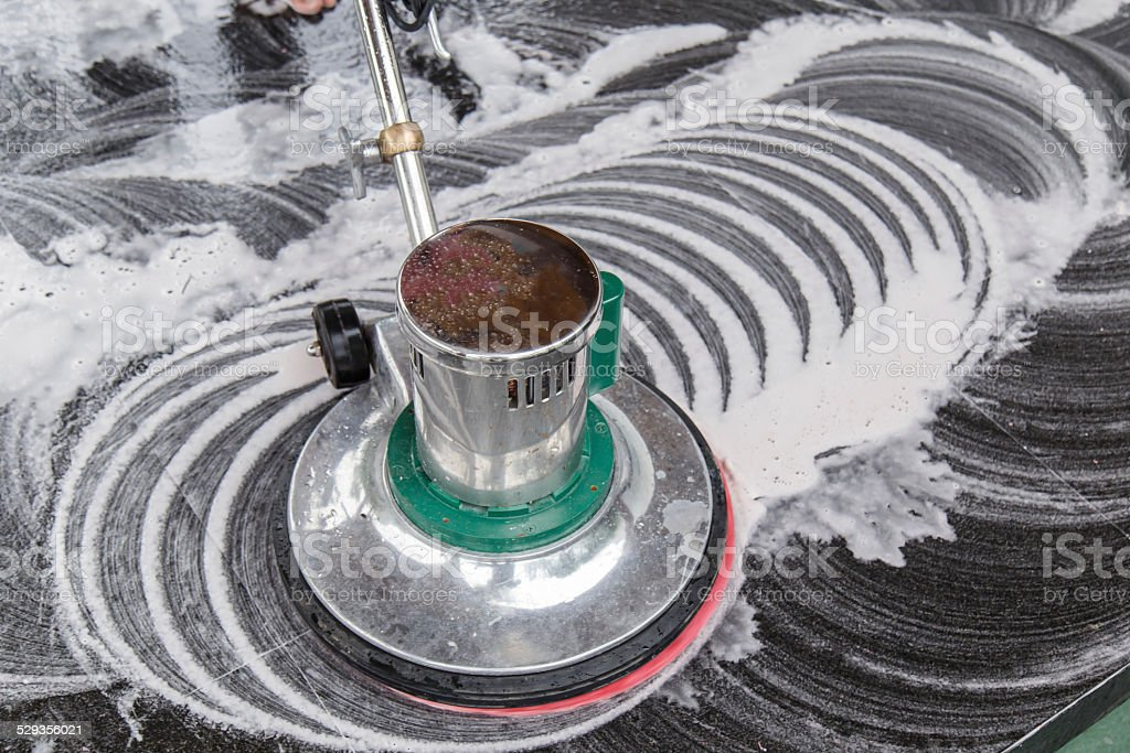Thai people cleaning black granite floor with machine and chemic stock photo