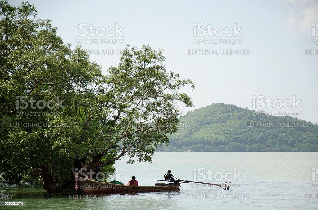 Thai people fisherman stop wooden fishing boat under tree stock photo