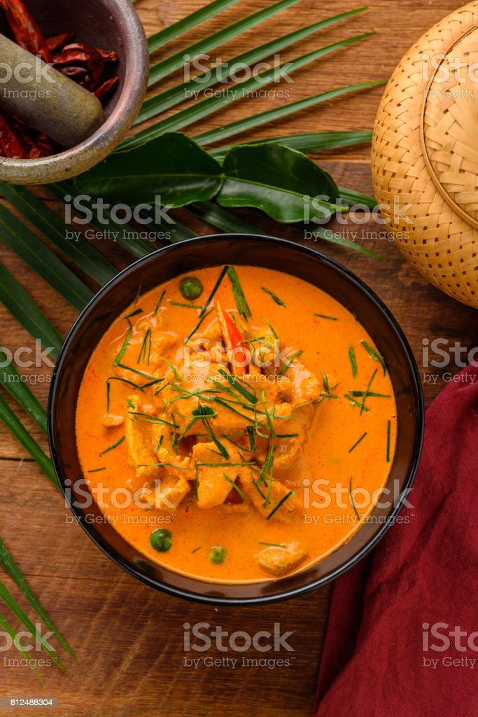 Thai red chicken curry on wooden table with ingredients decorate around. stock photo