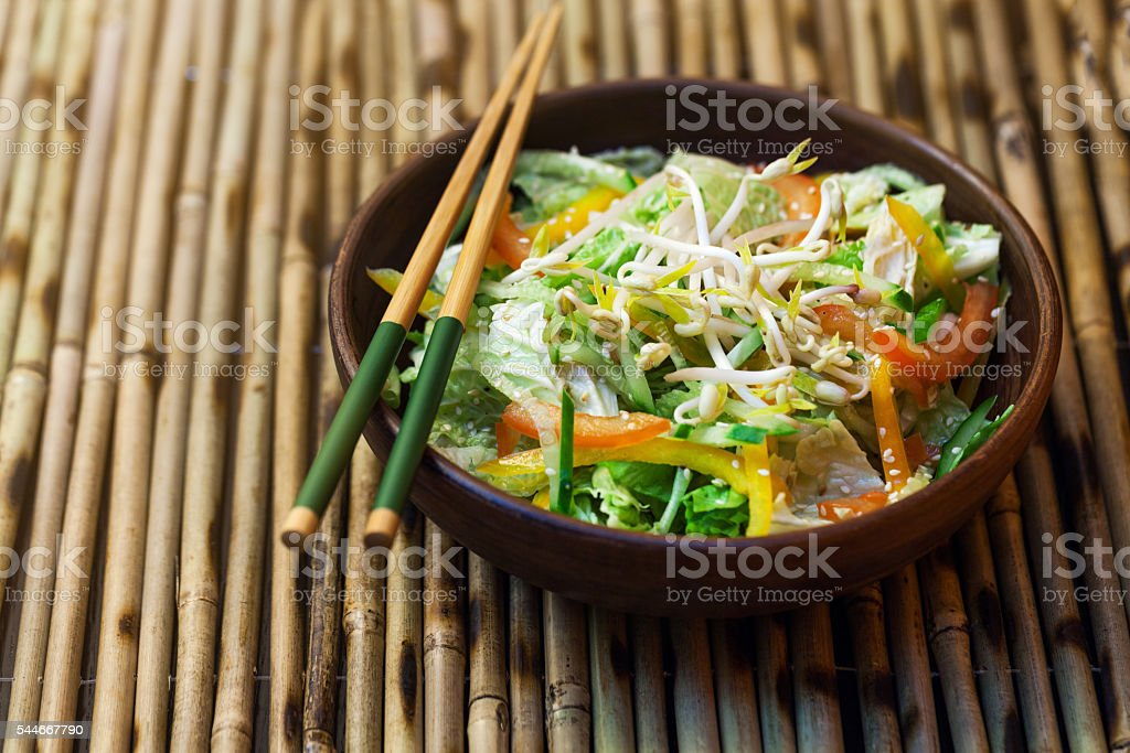 Thai salad with greens, vegetables and sprouts on a  table stock photo