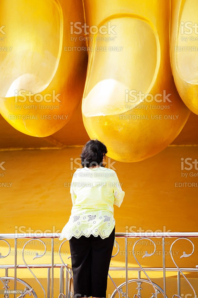Thai senior woman and huge fingers of buddha stock photo