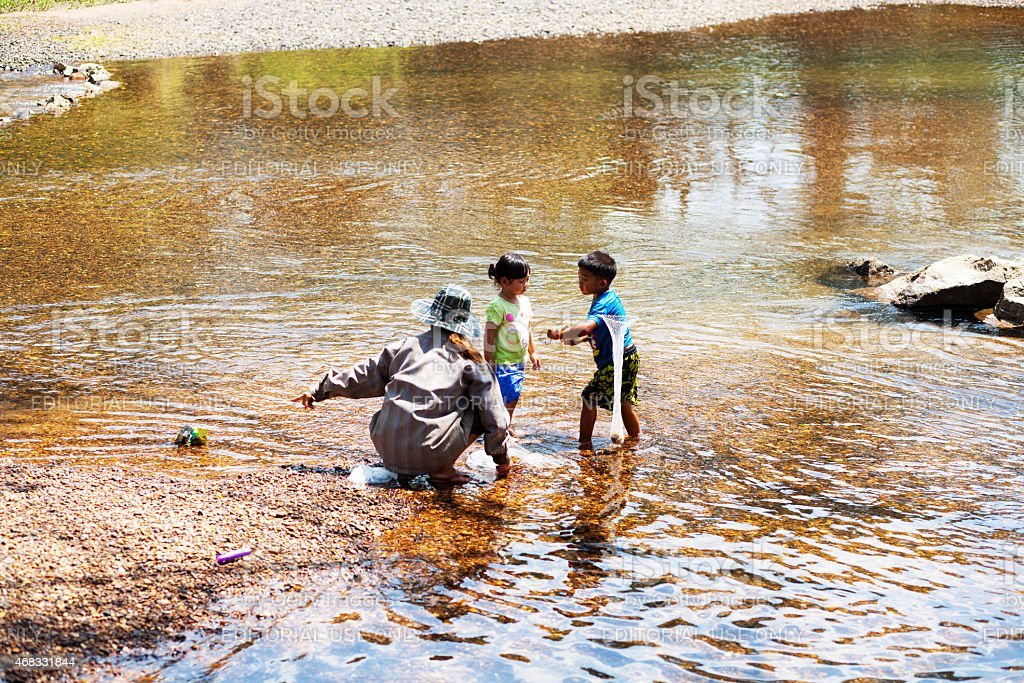 Thai senior woman with two kids in river Phetchaburi stock photo