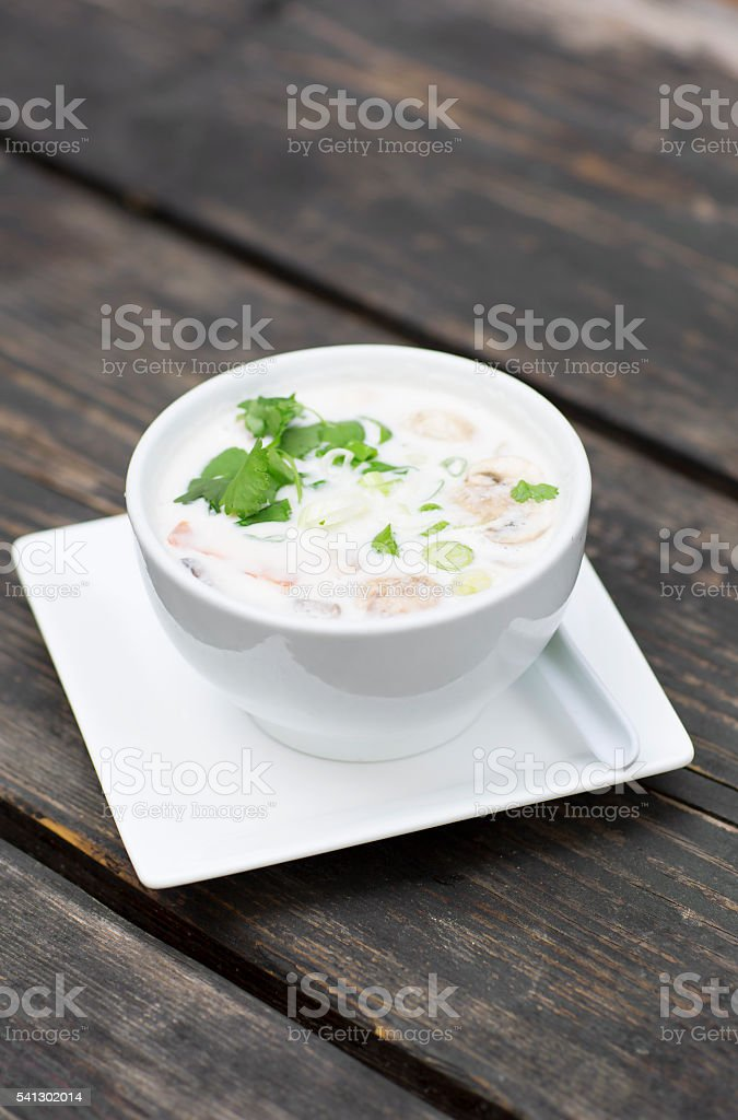 Thai soup in a white dish on a wooden table. stock photo