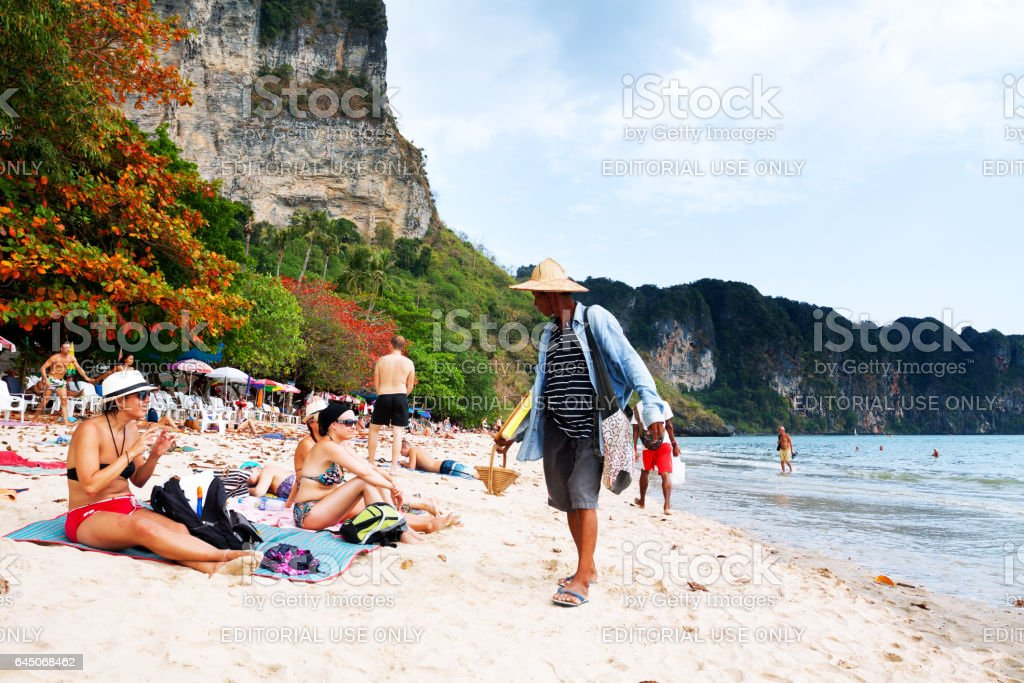 Thai souvenir vendor talking to female tourists on beach stock photo