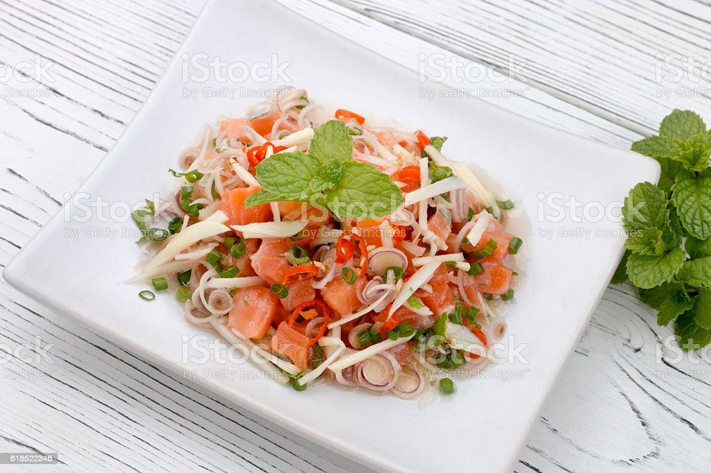 thai spicy salmon salad on wood table, thai food stock photo
