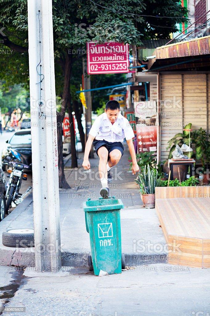 Thai student jumping over trash bin stock photo