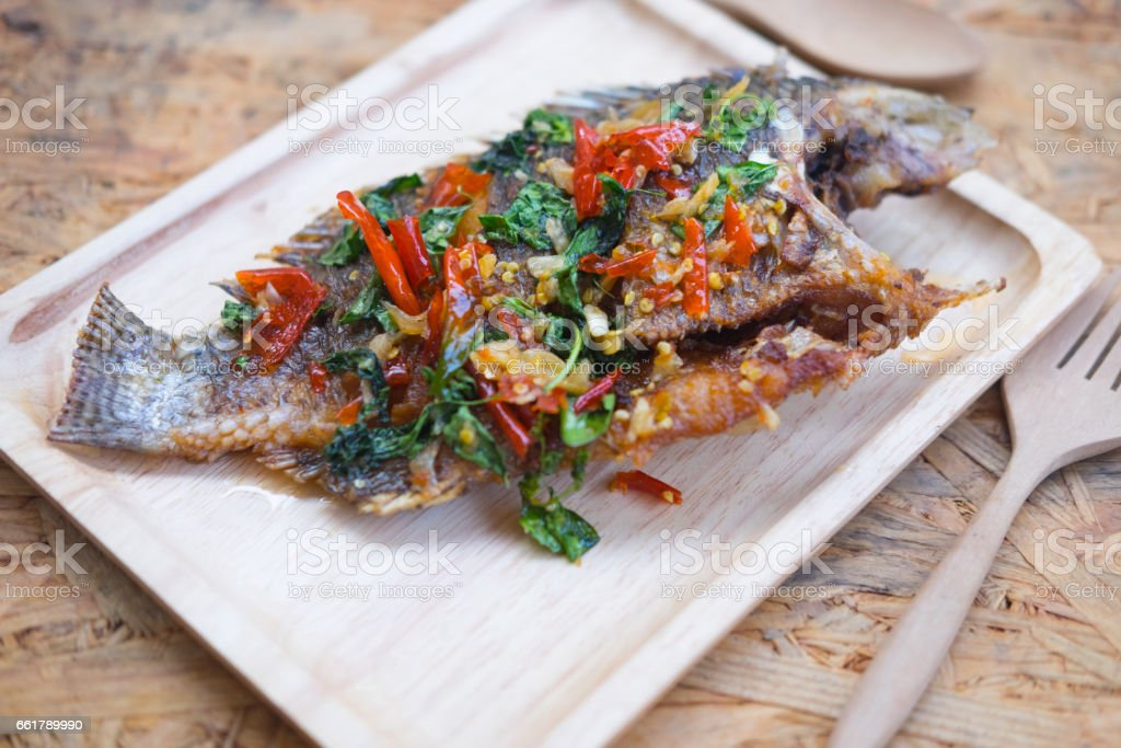 Thai style fish menu, deep fried in chili sweet sauce on wood tray stock photo
