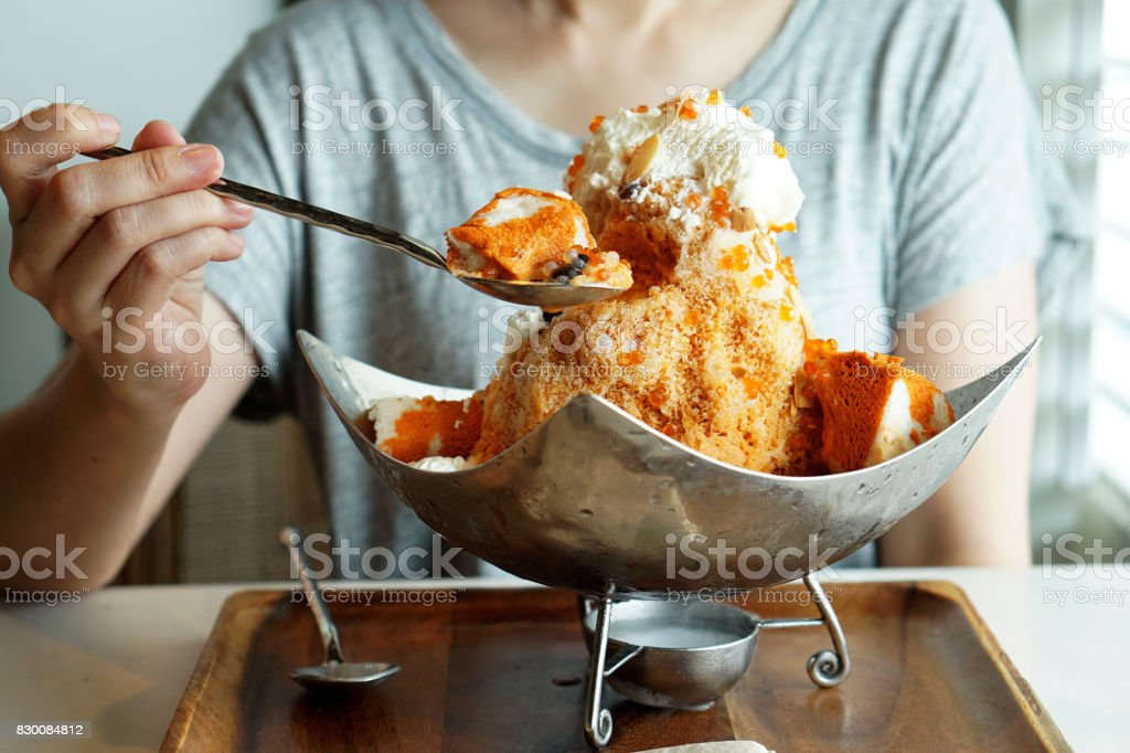 Thai Tea Shaved Ice served with bread, whipped cream, smaller spheres of white and orange boba (bubble tea), and generous sprinkle of toasted sliced almonds. stock photo
