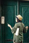 Thai Tourist Ringing on a Doorbell