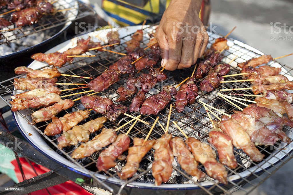 Thai vendor barbequing satay sticks royalty-free stock photo