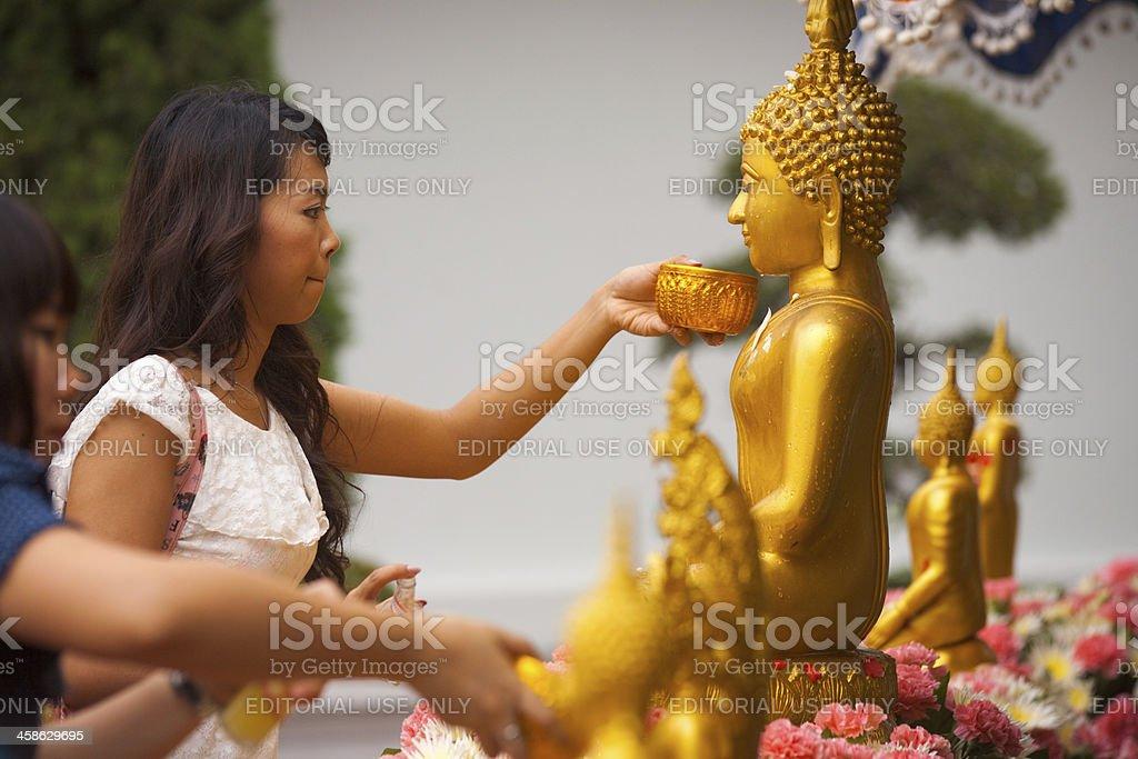 Thai Woman Bathing Buddha Statue royalty-free stock photo