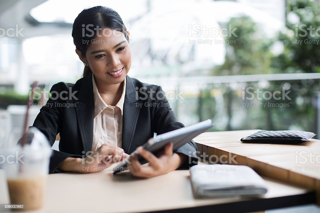Thai woman cheching her didgital tablet for app alerts. stock photo