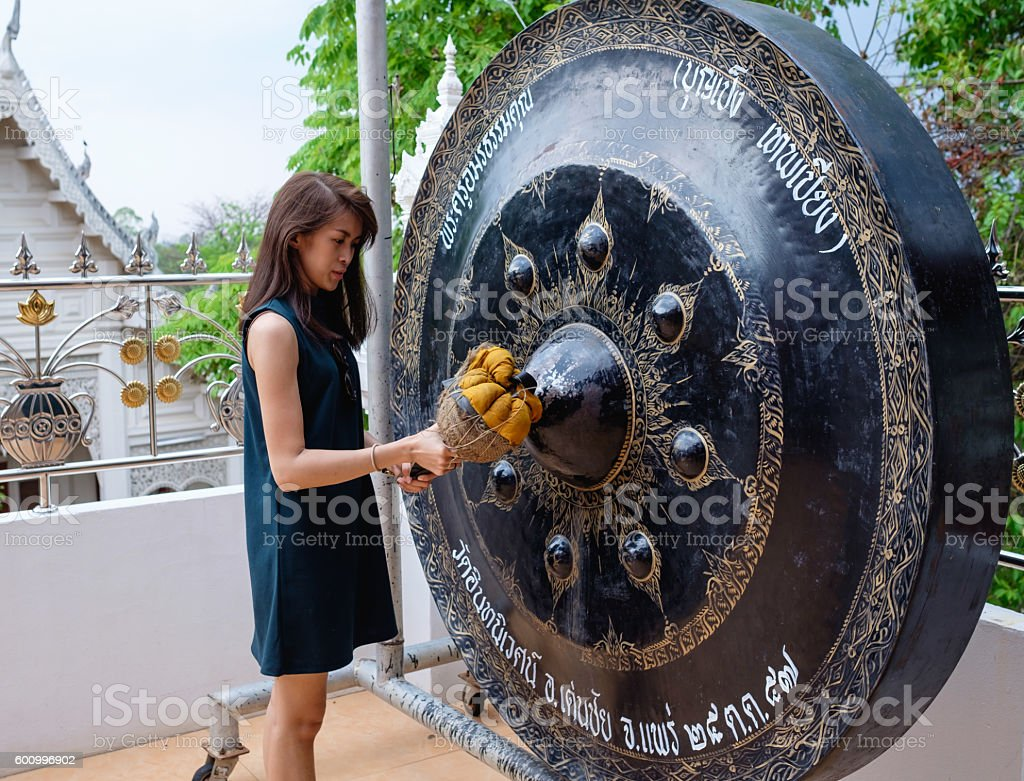 thai woman hold wooden hammer to hit big circle bell stock photo