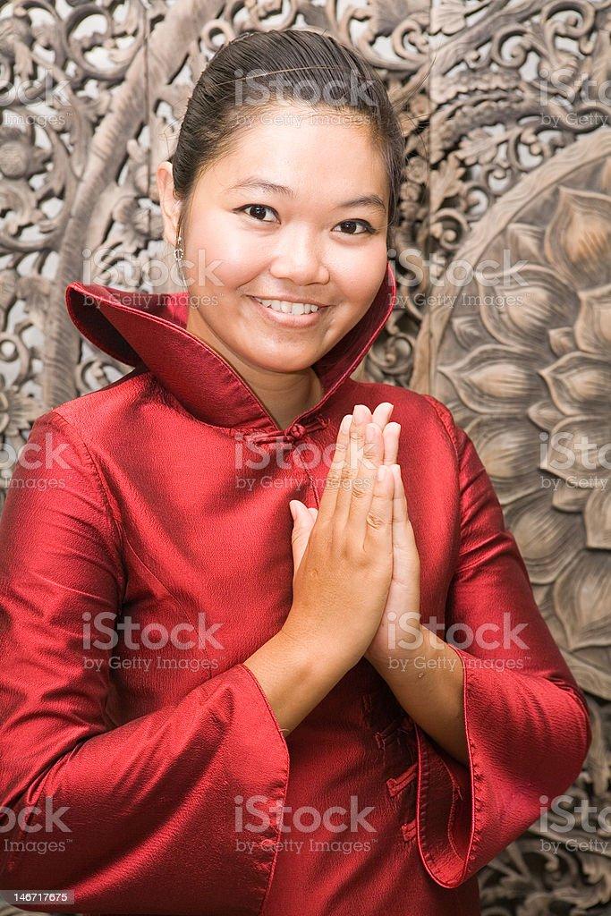 Thai woman in silk dress greeting stock photo