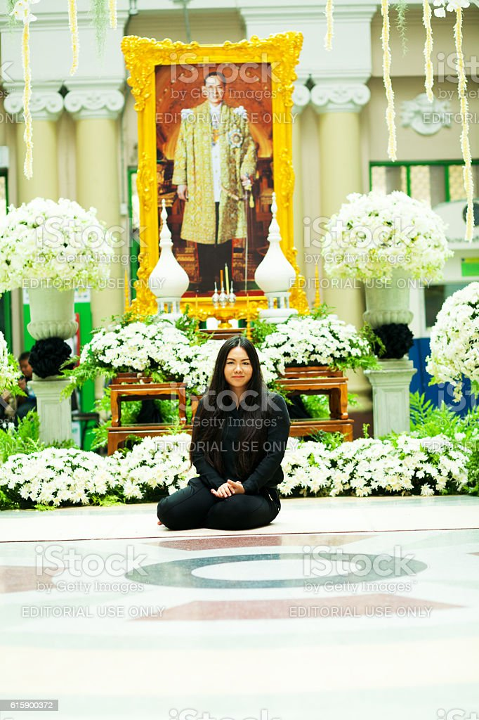 Thai woman sitting in front King Bhumipol's image stock photo