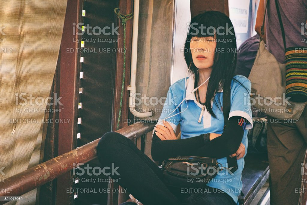 Thai woman sleeping and waiting for ferry arrival stock photo