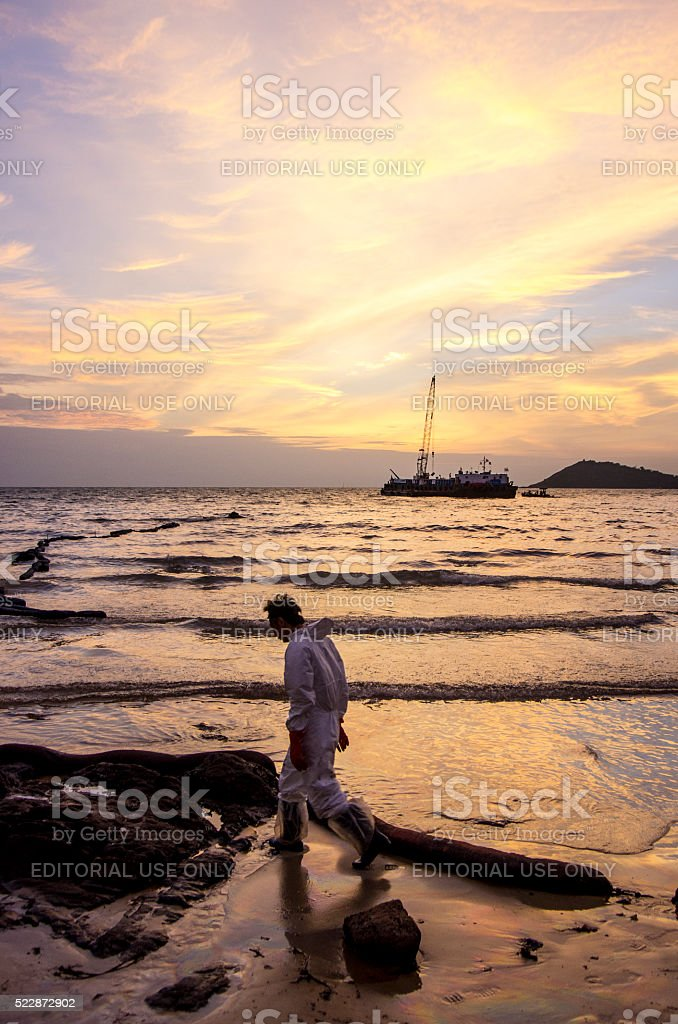 Thai workers at the beach during the oil spill. stock photo