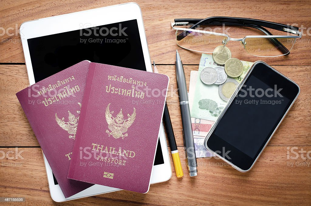 Thailand Passport with currency on teak wood . stock photo