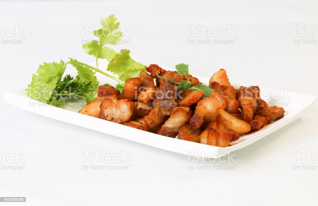 Thai's style deep fried pork belly on a white plate, white background. stock photo