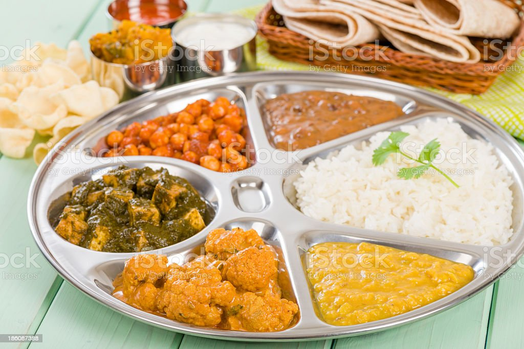 Thali with rice and vegetables on green painted wooden table stock photo