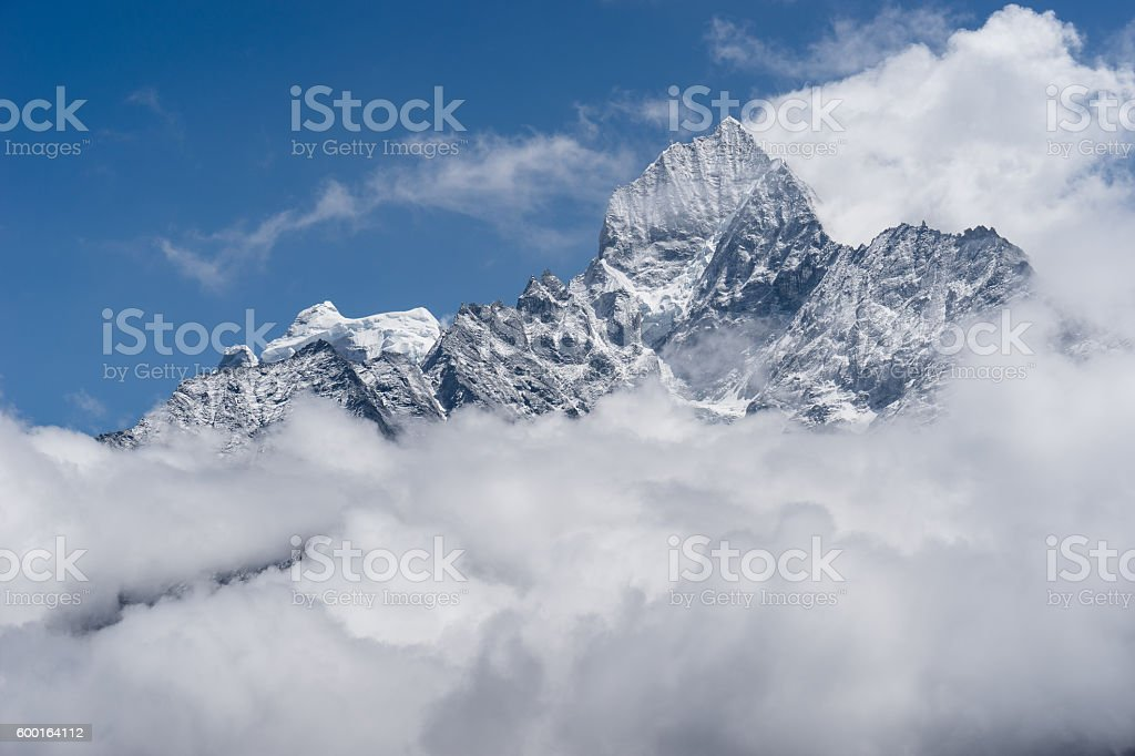 Thamserku mountain peak above the cloud stock photo