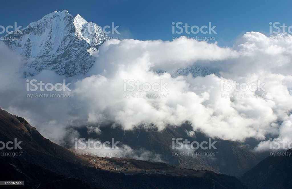 Thamserku peak, Phortse village and beautiful clouds royalty-free stock photo