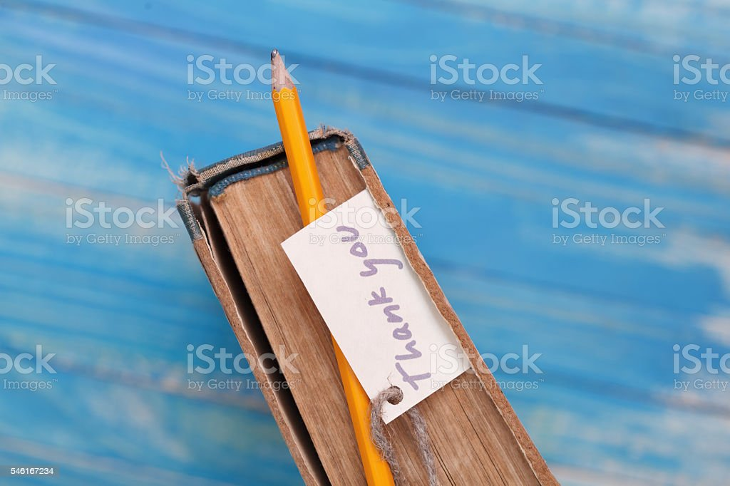 Thank you sign on pencil and old book stock photo