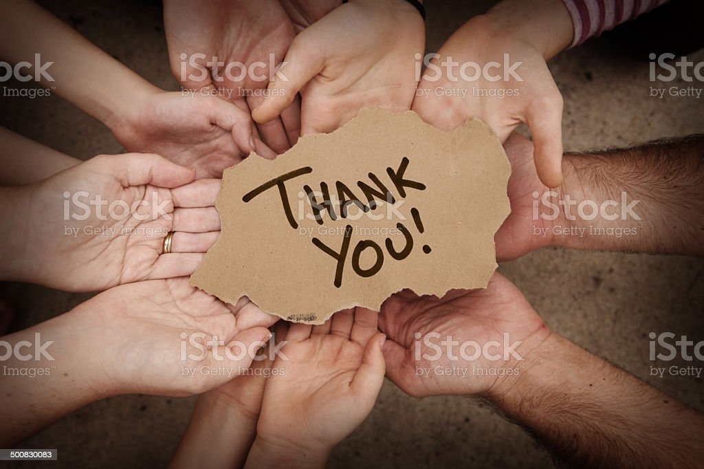 Thank You Written on Cardboard Being Held by Group stock photo