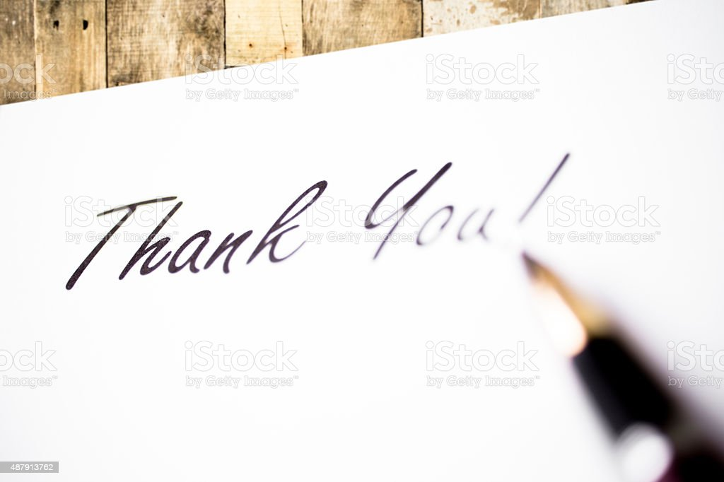 'Thank You' written on white paper. Wooden desk.  Pen. Office. stock photo