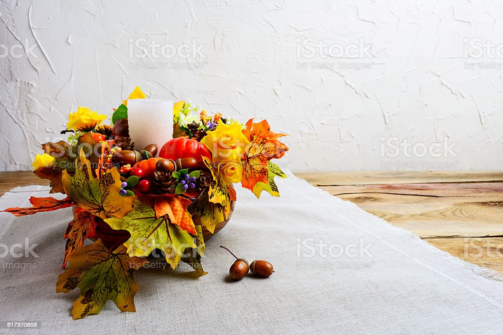 Thanksgiving centerpiece with decorated candle and silk fall lea stock photo
