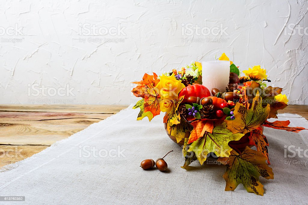 Thanksgiving centerpiece with white candle and silk fall leaves stock photo