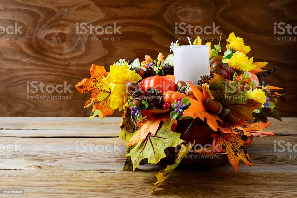 Thanksgiving decoration with white candle and silk fall leaves stock photo