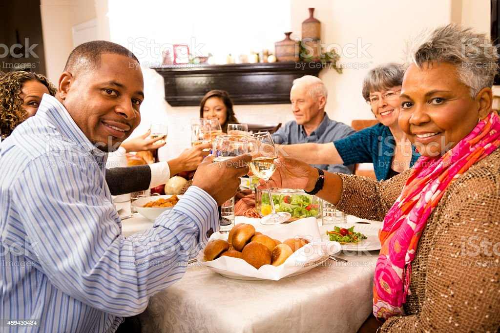 Thanksgiving: Family, friends gather for dinner at senior woman's home stock photo