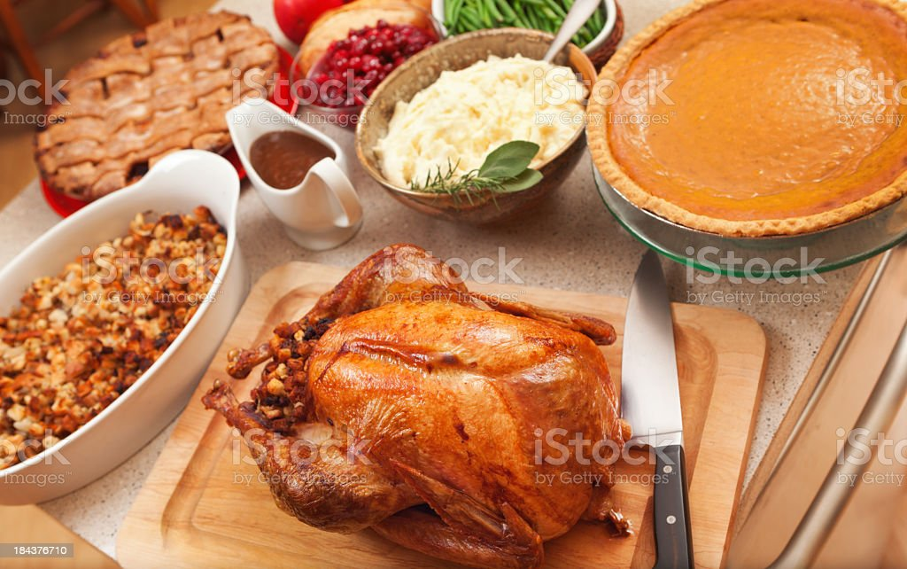 Thanksgiving Roast Turkey Dinner with Seasonal Holiday Foods in Kitchen stock photo