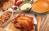 Thanksgiving Roast Turkey Dinner with Seasonal Holiday Foods in Kitchen