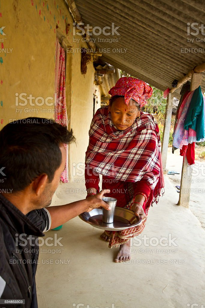 Tharu woman offering tea in nepali terai stock photo